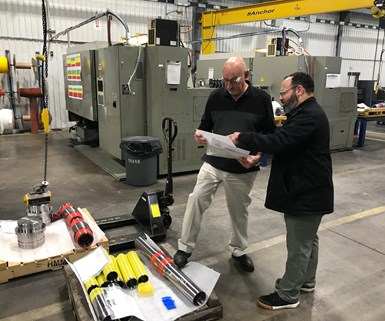 Todd Chretien (right), director of manufacturing at Superior Completion Services, consults with Hal Phillips, manufacturing manager.