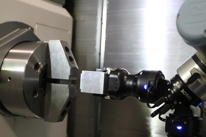 A robot loads a dovetailed blank into a chuck for CNC machining.