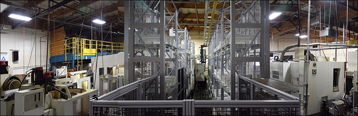 A view down a railway that transfers pallets to two five-axis CNC machining centers.
