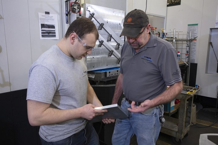 Shopfloor workers discuss a part at Tier One Machining LLC.