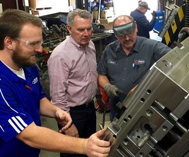 Don Dumoulin (second from left), owner and CEO of Precise Tooling Solutions in Indiana, evaluates a mold.