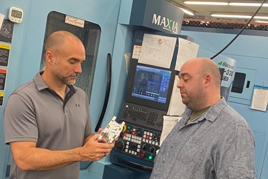 A picture of Matt Gawlik and Mat Rodde discussing a part
