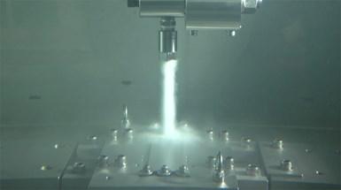 A jet of water shot-peens a metal part.