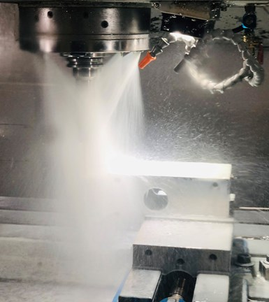 A close-up of the cutting zone of a vertical milling machine is obscured by a wash of nanocoolant that helps lubricate and cool the cutting zone.