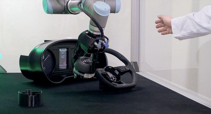 A hand breaks a light curtain and safety-stops a robot installing an airbag into a steering wheel.
