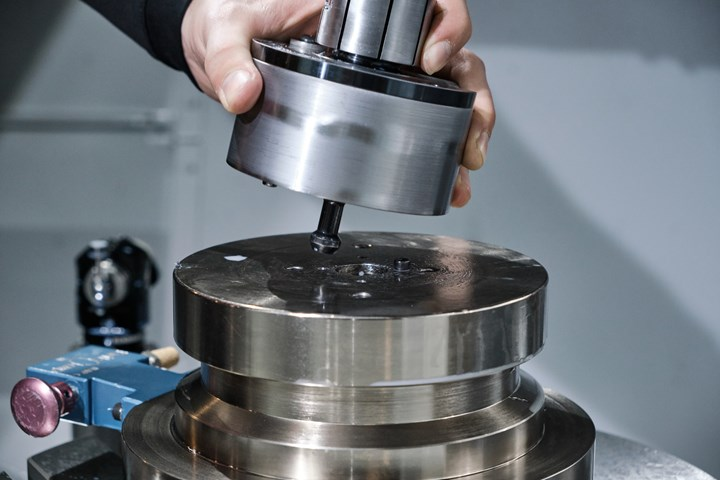 A machinist inserts a fixture equipped with Rimeco Products Kwik-Clamp quick-change system into a vertical CNC milling machine.