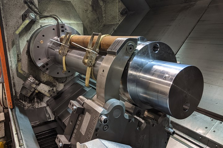 A large mandrel is set up on a lathe with a counterbalance for machining an off-center bore down its length.