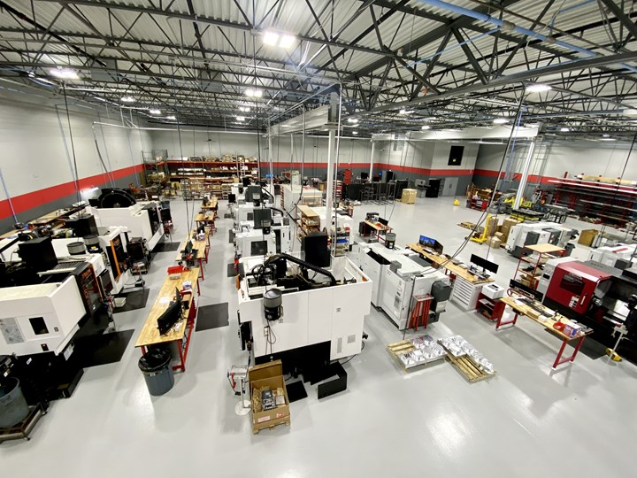 An overhead shot reveals a clean shop floor at Olson Custom Designs populated with sophisticated CNC machining centers and computers at every workstation.