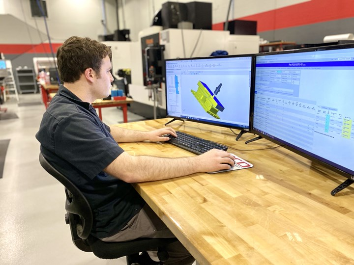 An employee at Olson Custom Designs works with CAD/CAM files at his shopfloor computer workstation.