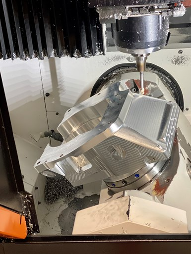 A close-up of a workpiece undergoing five-axis machining at Olson Custom Designs, a CNC machine shop producing defense department parts in Indianapolis.
