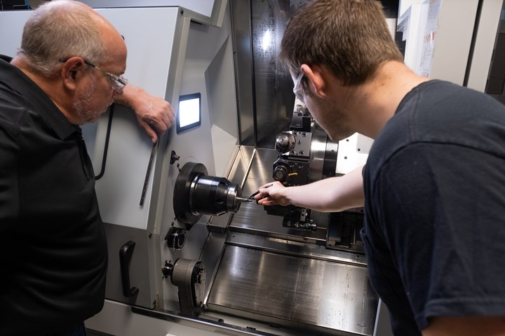 Personnel at Prosper-Tech check tooling in the turret of the CNC machine shop's new EuroTech Elite live-tool lathe.