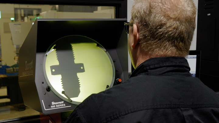An employee at Prosper-Tech Machine & Tool measures a machined part on an optical comparator.