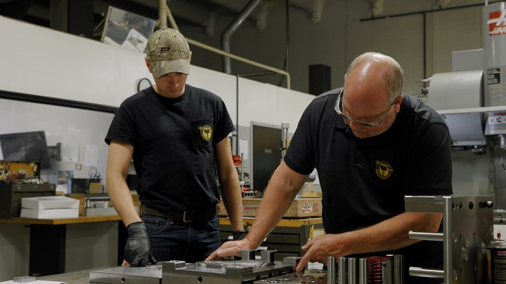 Bob Devroy and Roy LASTNAME examine parts on the shop floor of Prosper-Tech Machine & Tool.