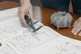 worker checking measurements between a CAD drawing and a 3D-printed part