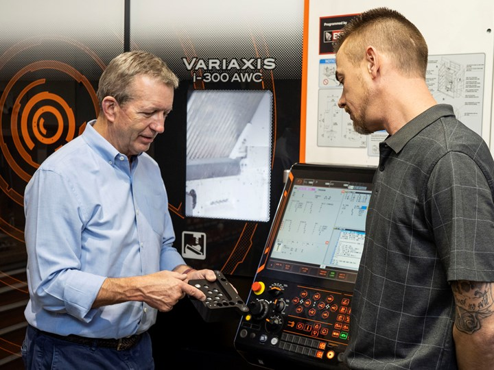 Grady Cope (left) shows David Hartfelder an aluminum workpiece with black anodizing to verify the absence of visible rack marks from the finishing process