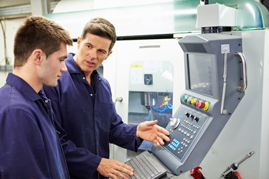 A stock photo showing one man training another one a machine