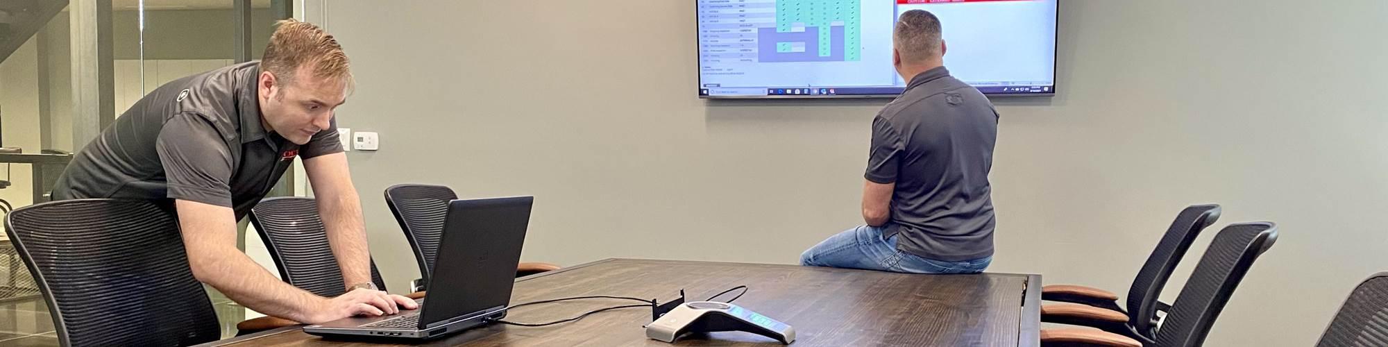 会议室里的人们在电脑上工作,看着墙上的屏幕。