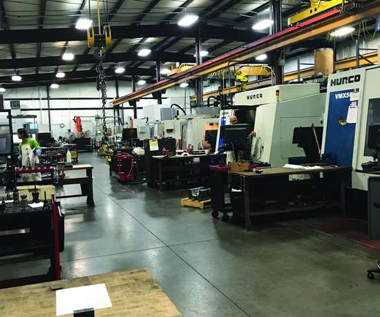 A shop floor lined with Hurco vertical machining centers as well as mold repair equipment
