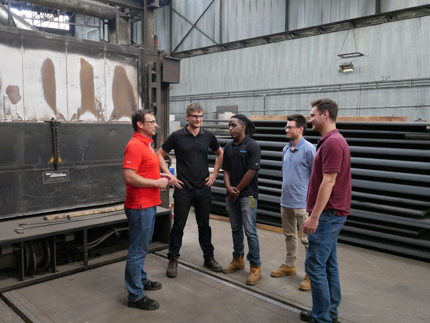 Professor teaching apprentices about furnaces