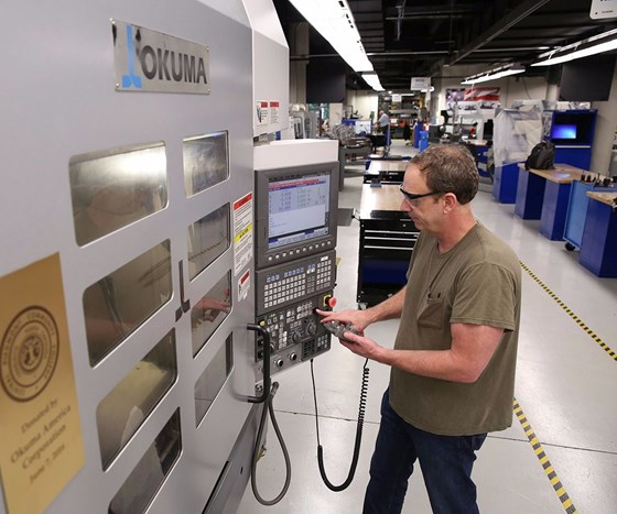 Machinist works on CNC vertical machining center