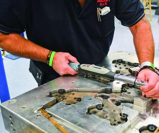 Worker torquing manifold bolts