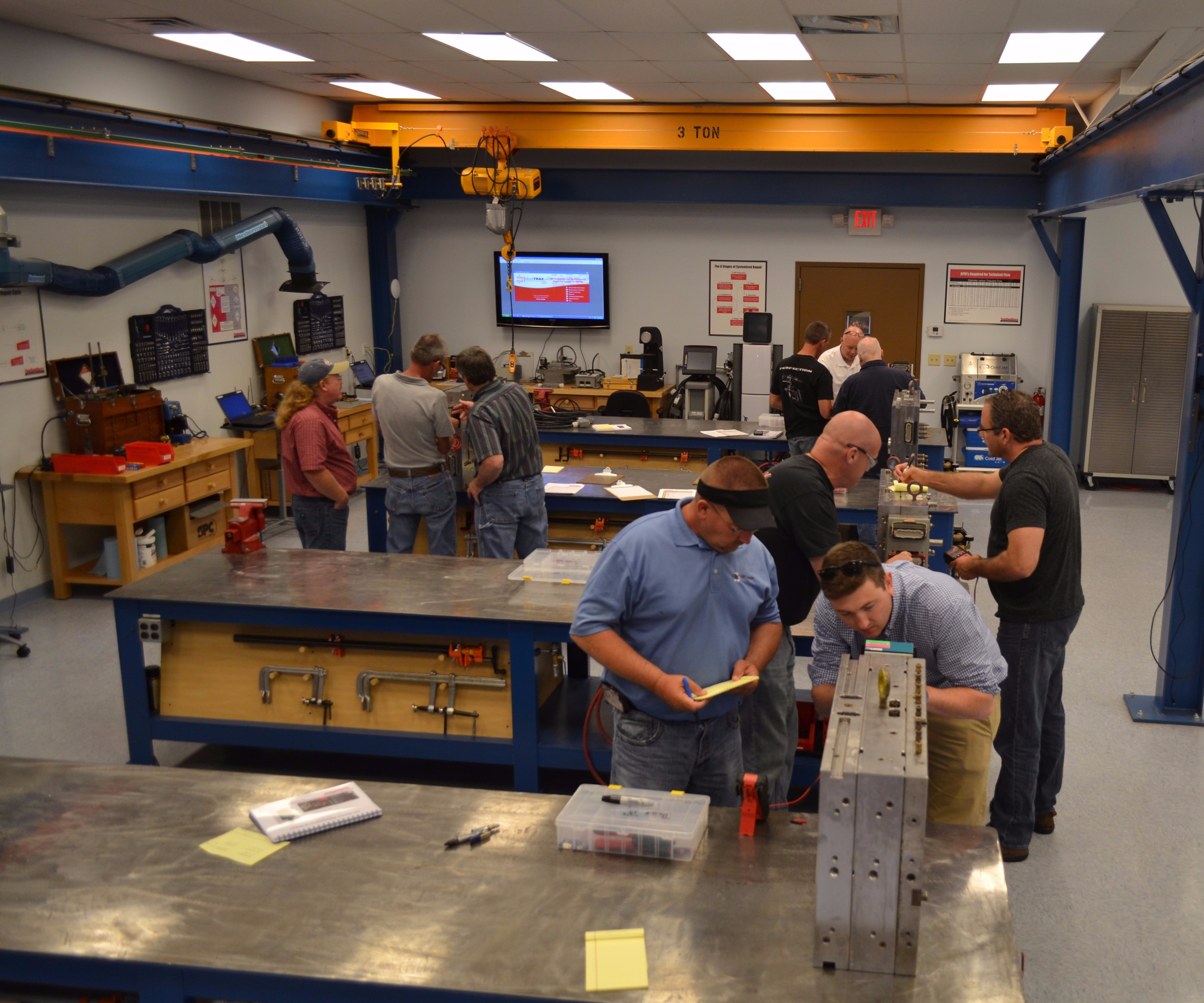 Student pairs and trainers work on molds during training course.
