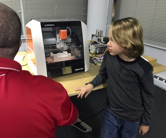 Seven-year-old Leo Fisher learns about CNC milling at American Mold Builders Association meeting.