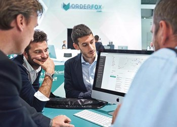 Professionals gather around a computer with Orderfox interface at EMO 2017