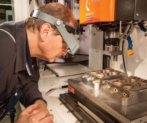Janler moldmaker and EDM expert Karle Lang inspects the intricate mold details produced on the shop's GF AgieCharmilles FORM 350 SP sinker EDM unit