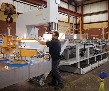 worker processes the next generation of aluminum mold material on a metal-cutting saw