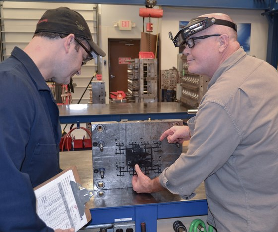 A mold technician is pointing to a problem on an ejected part from a mold to a process engineer