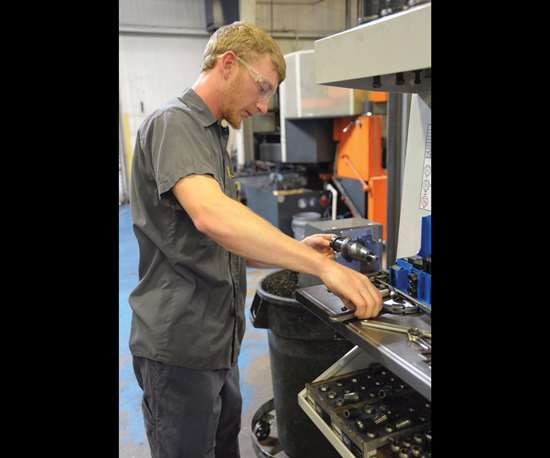 apprentice Hoke Durham works on a CNC setup