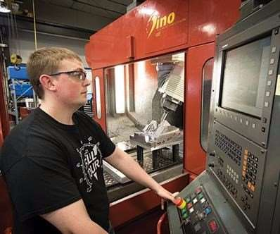 Machinist operates FPT Dino high-speed, five-axis, bridge-style CNC mill