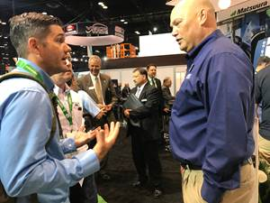two men talking on trade show floor
