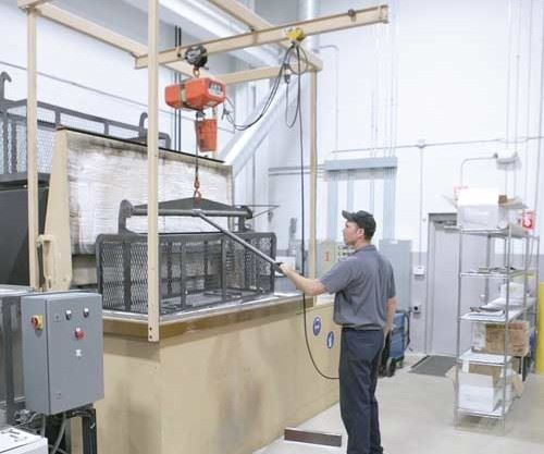 Worker puts mold components into a fluidized bed for cleaning