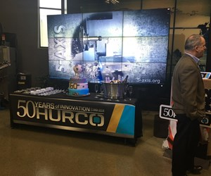 Hurco 50th display with a banner, video and cake