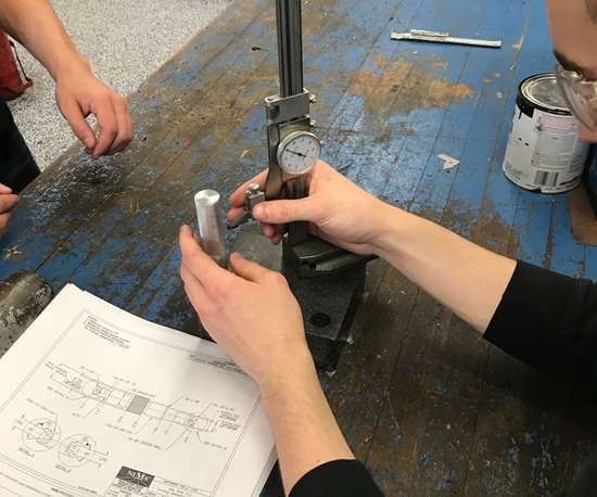Using a height gauge to measure a workpiece in advanced manufacturing.