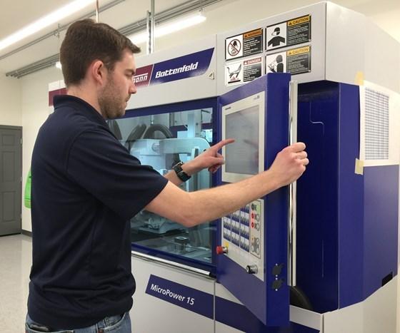 Person operating Wittmann Battenfeld 15t press