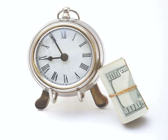 clock with a roll of U.S. one hundred dollar bills tied with an elastic stacked up against it