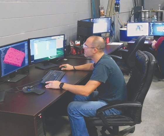 Programmer at computer station working on CAD/CAM software.