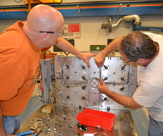 men working on hot runner manifold