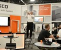 Hasco employee standing on a chair and playing a trumpet in Hasco booth at Amerimold 2018