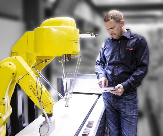 FANUC employee working with FANUC robots on a tablet