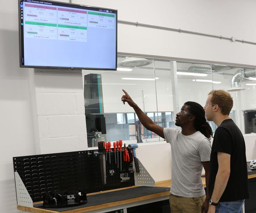 men looking at wall monitor