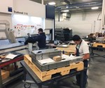 Fredy Nevas (right) helps form laser-cut parts on the company's press brake.