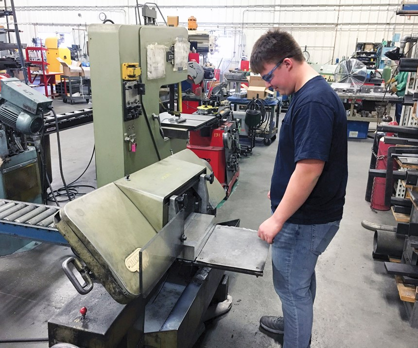 Student cuts stock for a new project on a bandsaw