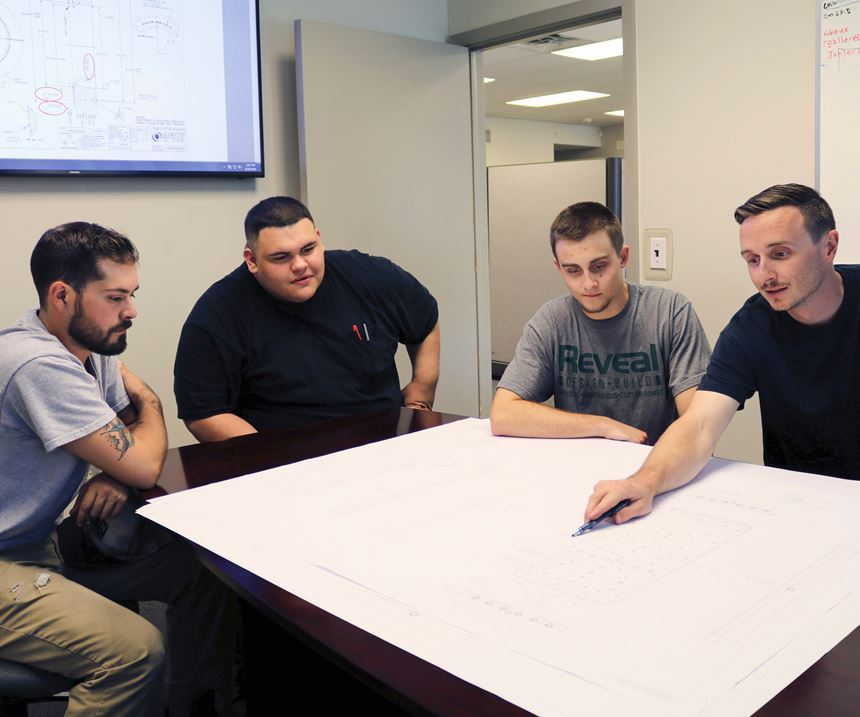 Apprentices at Janler Corp. in Chicago sitting around a table in a conference room