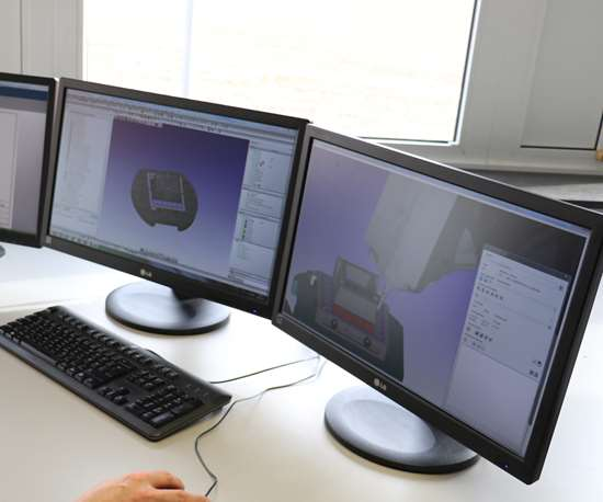 3 computer screens showing software, a keyboard and a hand over the mouse