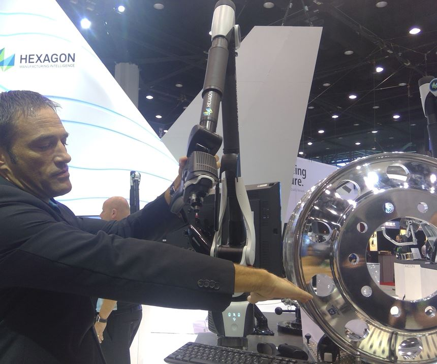 Hexagon Manufacturing Intelligence employee showing the Absolute Arm on display