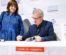 Terry Iverson signing his book, Finding America's Greatest Champion